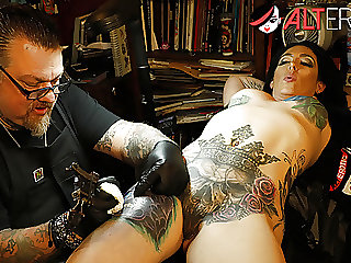 Marie Bossette touches herself while being tattooed